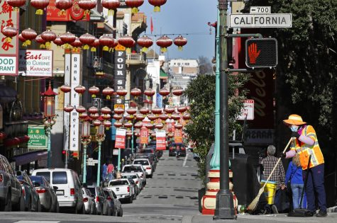 FILE - In this Jan. 31, 2020, file photo, a masked worker cleans a street in the Chinatown district in San Francisco. Police are stepping up patrol and volunteers are increasing their street presence after several violent attacks on older Asians stoked fear in the San Francisco Bay Area