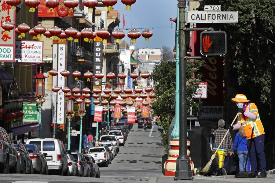 FILE - In this Jan. 31, 2020, file photo, a masked worker cleans a street in the Chinatown district in San Francisco. Police are stepping up patrol and volunteers are increasing their street presence after several violent attacks on older Asians stoked fear in the San Francisco Bay Area's Chinatowns and subdued the celebratory mood leading up to Chinese New Year. (AP Photo/Ben Margot, File)