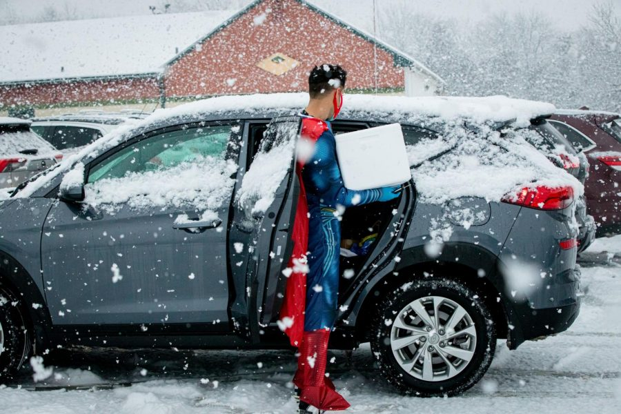 Mayank Amin, dressed as Superman, helps patients out of the car, carrying a box of doses of the COVID-19 vaccine.