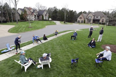 Neighbors have an informal gathering while keeping a safe distance because of the corona virus Sunday, March 22, 2020, in Nolensville, Tenn. (AP Photo/Mark Humphrey)