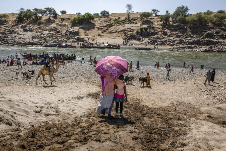 FILE - In this Nov. 21, 2020, file photo, refugees who fled the conflict in Ethiopia's Tigray region arrive on the banks of the Tekeze River on the Sudan-Ethiopia border, in Hamdayet, eastern Sudan. Huge unknowns persist in the deadly conflict, but details of the involvement of neighboring Eritrea, one of the world's most secretive countries, are emerging with witness accounts by survivors and others. (AP Photo/Nariman El-Mofty, File)