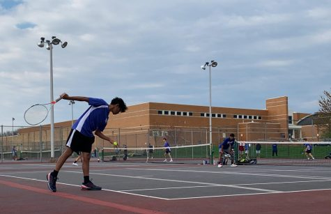 Nikhil Madaka (12) preparing a serve during a doubles match, assisted by Jigar Dadarwala (12) at a April 15th match.